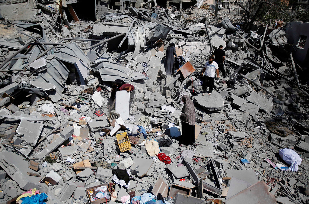 Description of . Palestinians search the rubble their home in Beit Hanoun, Gaza Strip, Friday, Aug. 1, 2014. A three-day Gaza cease-fire that began Friday quickly unraveled, with Israel and Hamas accusing each other of violating the truce. (AP Photo/Hatem Moussa)