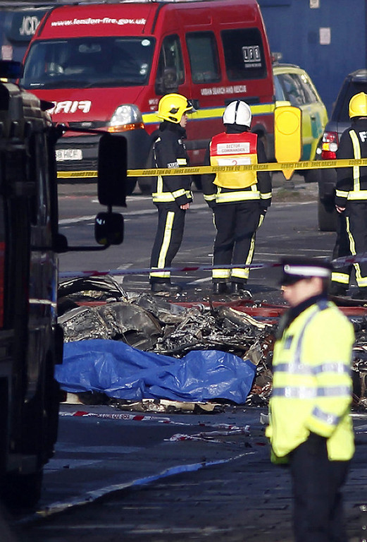 . Debris is pictured in front of a fire engine at the scene of a helicopter crash in central London on January 16, 2013. Two people were killed when a helicopter hit a crane at a building site in central London during morning rush hour and plunged to the ground, engulfing several cars in flames.   JUSTIN TALLIS/AFP/Getty Images