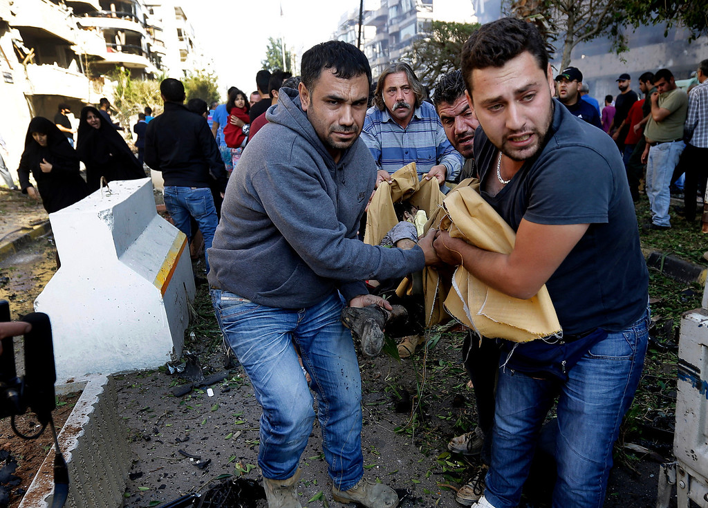 Description of . Lebanese citizens carry a dead body, at the scene where two explosions have struck near the Iranian Embassy killing many, in Beirut, Lebanon, Tuesday Nov. 19, 2013.  (AP Photo/Hussein Malla)