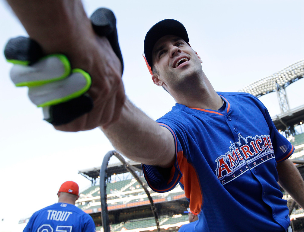 Description of . American League's Joe Mauer, of the Minnesota Twins, shakes hands with a spectator befor batting practice for the MLB All-Star baseball game, on Tuesday, July 16, 2013, in New York. (AP Photo/Kathy Willens)