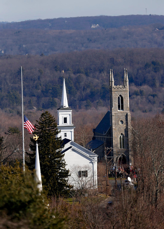 Description of . With a U.S. flag waving at half-staff, left, people are seen congregated in front of  Trinity Episcopal Church, right, during funeral services for Benjamin Andrew Wheeler,  Thursday, Dec. 20, 2012, in Newtown, Conn. Wheeler, 6, died when the gunman, Adam Lanza, walked into Sandy Hook Elementary School in Newtown, Conn., Dec. 14, and opened fire, killing 26 people, including 20 children, before killing himself. (AP Photo/Julio Cortez)