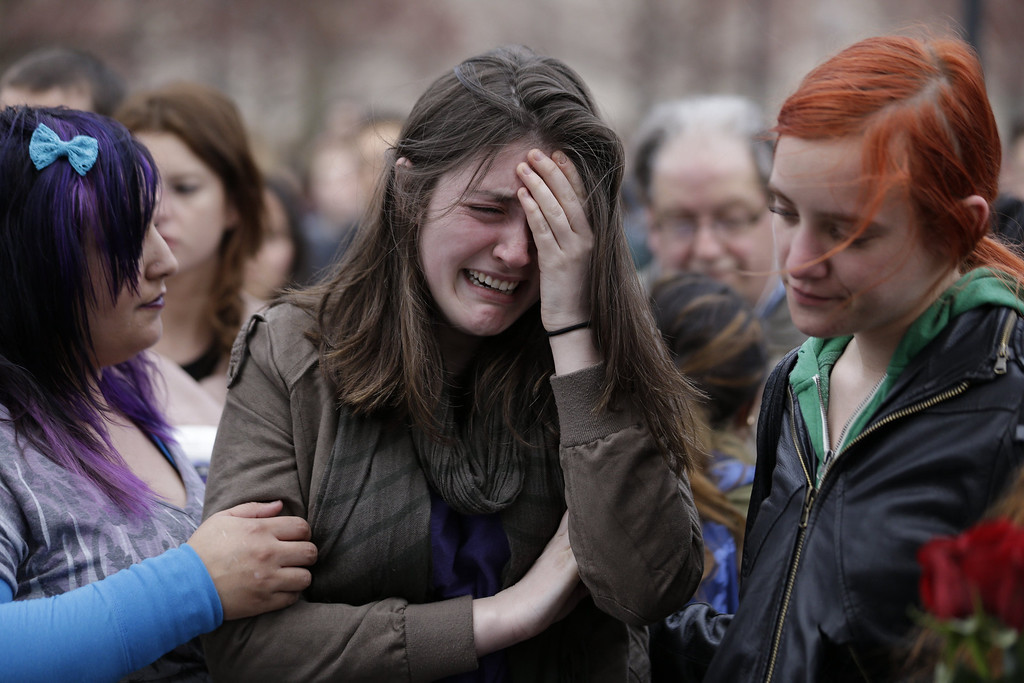 Description of . Emma MacDonald, 21, center, cries during a vigil for the victims of the Boston Marathon explosions at Boston Common, Tuesday, April 16, 2013. Twin explosions near the marathon's finish line Monday killed three people, wounded more than 170 and reawakened fears of terrorism. (AP Photo/Julio Cortez)