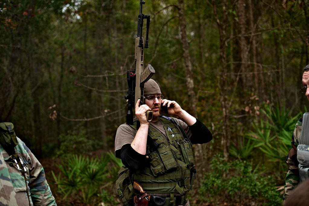 ". A member of the North Florida Survival Group takes a break from performing an enemy contact drill to call his wife during a field training exercise in Old Town, Florida, December 8, 2012.The group trains children and adults alike to handle weapons and survive in the wild. The group passionately supports the right of U.S. citizens to bear arms and its website states that it aims to teach ""patriots to survive in order to protect and defend our Constitution against all enemy threats\"".    Picture taken December 8, 2013.   REUTERS/Brian Blanco"