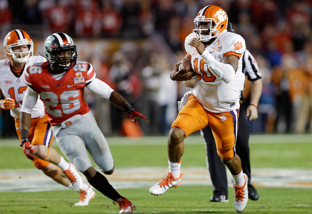 Description of . Clemson quarterback Tajh Boyd (10) runs on his way to scoring a touchdown as Ohio State cornerback Armani Reeves (26) defends during the first half of the Orange Bowl NCAA college football game, Friday, Jan. 3, 2014, in Miami Gardens, Fla. (AP Photo/Lynne Sladky)