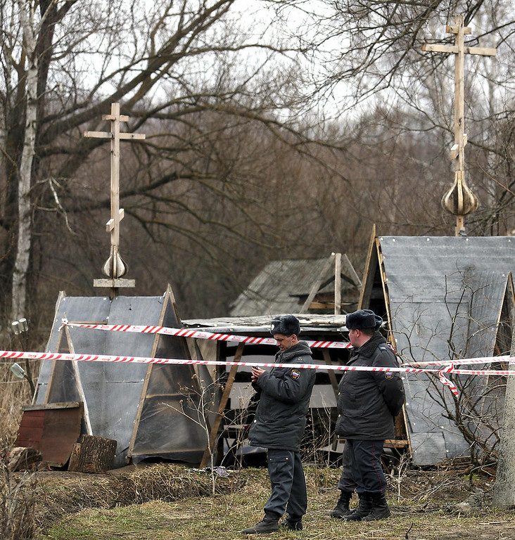 Description of . Two policemen guard a house of a doomsday sect in the village of Nikolskoye on April 2, 2008. Three of the last 14 members of a Russian doomsday sect left their muddy cave on Wednesday after five months barricaded underground waiting for the Apocalypse.
