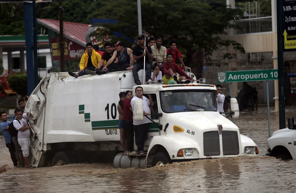 Description of . Residents attempt to leave the flooded area in Acapulco, Guerrero state, Mexico, after heavy rains hit the area on September 16, 2013. Hurricane Ingrid weakened to tropical storm strength as it made landfall on the northeastern coast in the morning while the Pacific coast was reeling from the remnants of Tropical Storm Manuel, which dissipated after striking on the eve. Thousands of people were evacuated on both sides of the country as the two storms set off landslides and floods that damaged bridges, roads and homes.   Pedro PARDO/AFP/Getty Images