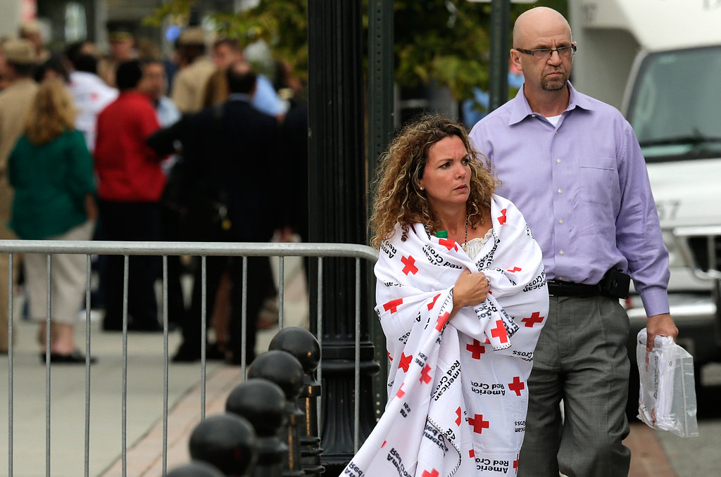 Description of . A woman wrapped in a Red Cross blanket leaves a gathering point for reuniting family members of Navy Yard employees that was set up inside Nationals Park in the wake of the shooting September 16, 2013 in Washington, DC. Police believe at least one gunman shot and killed at least 12 people and wounded others in an incident that put parts of the city on lockdown. (Photo by Win McNamee/Getty Images)