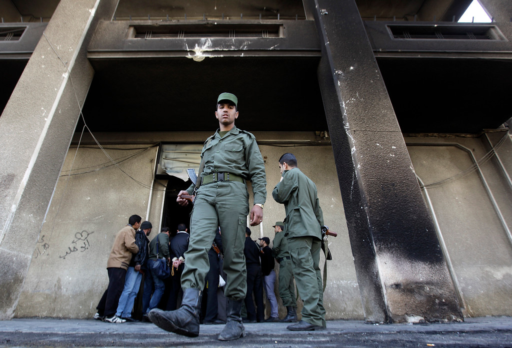 Description of . A Syrian army soldier steps out from the burned court building that was set on fire by Syrian anti-government protesters, in the southern city of Daraa, Syria, on Monday March 21, 2011. Mourners chanting