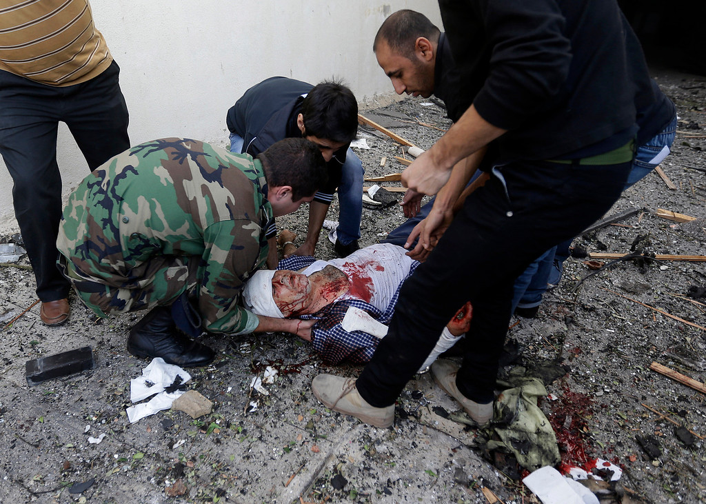 Description of . A Lebanese soldier and citizens help an injured man on the ground, at the scene where two explosions have struck near the Iranian Embassy killing many, in Beirut, Lebanon, Tuesday Nov. 19, 2013.  (AP Photo/Hussein Malla)