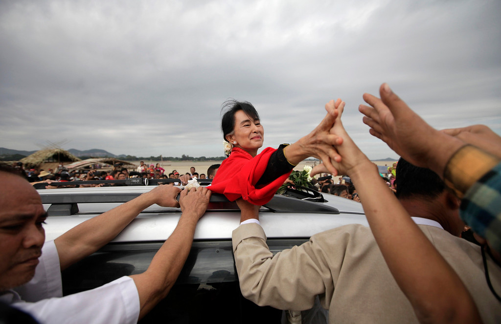 Description of . Myanmar pro-democracy leader Aung San Suu Kyi shakes hands with supporters after giving a speech in Monywa November 30, 2012. Suu Kyi offered to mediate between company officials and those who are opposing a vast copper mining project after riot police fired water cannon and tear gas on Thursday to break up a three-month protest against the project run by the powerful Myanmar military and its partner, a subsidiary of a Chinese arms manufacturer. Activists said at least 50 people had been injured and 23 were in hospital, some suffering burns after incendiary devices were hurled into their camps by police.  REUTERS/Soe Zeya Tun