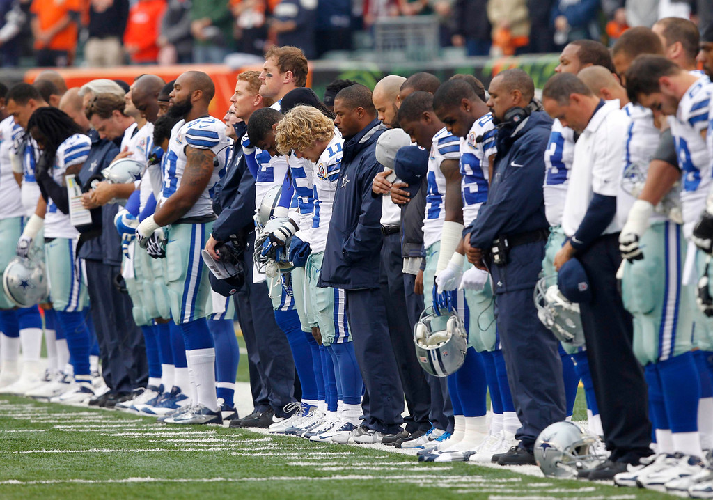 Description of . Dallas Cowboys players hang their heads during a moment of silence honoring teammate Jerry Brown who was killed in an automobile accident, prior to an NFL football game against the Cincinnati Bengals at Paul Brown Stadium in Cincinnati, Ohio, December 9, 2012.       REUTERS/John Sommers II