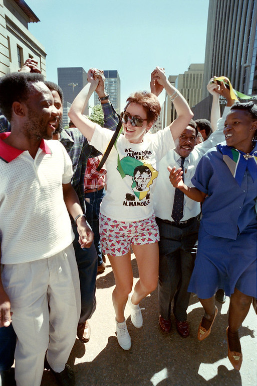 Description of . People dance in central Johannesburg street on February 23, 1990 as hundreds of Democratic Party supporters marched for Democracy to city hall to hear speeches by party leaders who had met earlier with African National Congress leader Nelson Mandela. (Photo credit should read ALEXANDER JOE/AFP/Getty Images)