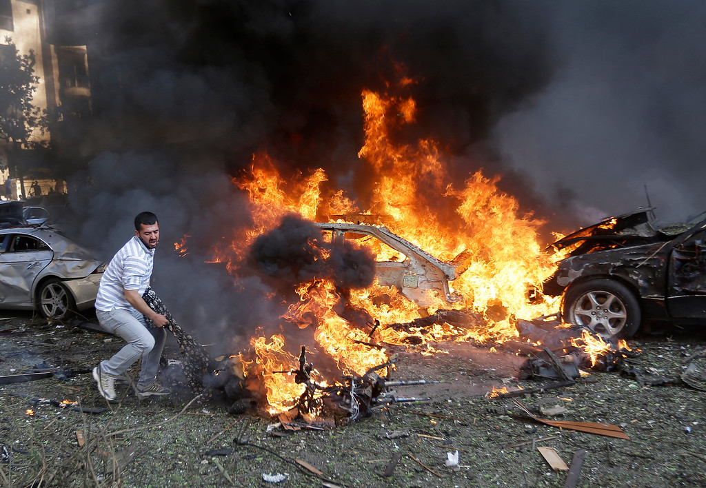 Description of . A Lebanese man tries to pull a dead body out of a burned car, at the scene where two explosions have struck near the Iranian Embassy killing several, in Beirut, Lebanon, Tuesday, Nov. 19, 2013. The blasts in south Beirut\'s neighborhood of Janah also caused extensive damage on the nearby buildings and the Iranian mission. The area is a stronghold of the militant Hezbollah group, which is a main ally of Syrian President Bashar Assad in the civil war next door. It\'s not clear if the blasts are related to Syria\'s civil war. (AP Photo/Hussein Malla)