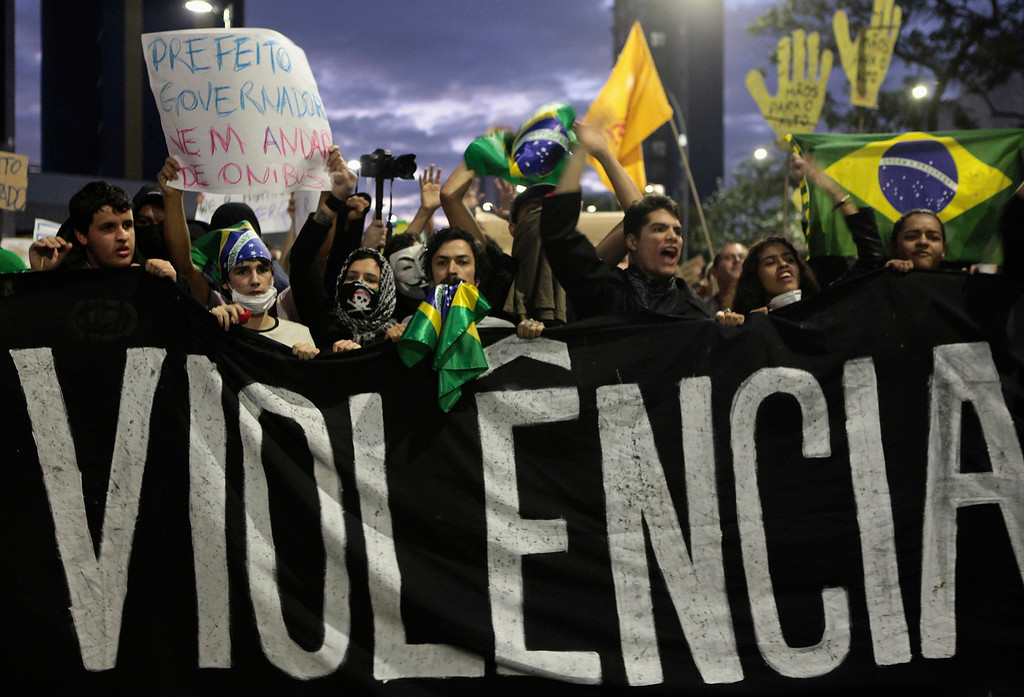 Description of . Demonstrators shout anti-government slogans behind a banner, which reads as 'violence', during one of many protests around Brazil's major cities in Sao Paulo June 17, 2013. Tens of thousands of demonstrators marched through the streets of Brazil's biggest cities on Monday in a growing protest that is tapping into widespread anger at poor public services, police violence and government corruption. REUTERS/Alex Almeida (BRAZIL - Tags: CIVIL UNREST POLITICS)