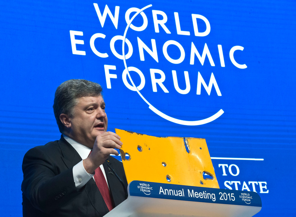 Description of . Ukrainian President Petro Poroshenko shows a piece of a Bus that was attacked recently during the panel
