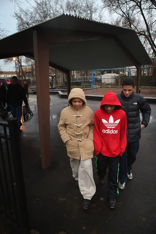 . Ten-year-old Nathaniel Pendleton (L) walks with family members under the shelter at a neighborhood park where his sister Hadiya was killed on January 30, 2013 in Chicago, Illinois. Fifteen-year-old Hadiya was shot and killed when a gunman opened fire in the park yesterday while she was hanging out with friends on the warm rainy afternoon under a shelter in the park. Hadiya was a majorette in her high school band and recently performed in Washington, D.C. during the inauguration. President Obama\'s Chicago home is less than a mile from the park where Hadiya was killed.   Another person was wounded in the leg during the shooting.   (Photo by Scott Olson/Getty Images)