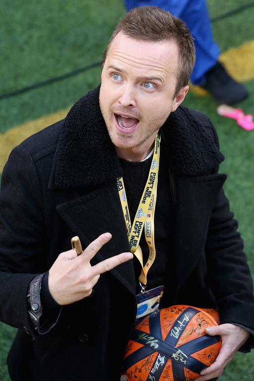 Description of . Actor Aaron Paul  signs an autograph before the start of Super Bowl XLVIII between the Denver Broncos and the Seattle Seahawks at MetLife Stadium on February 2, 2014 in East Rutherford, New Jersey.  (Photo by Christian Petersen/Getty Images)