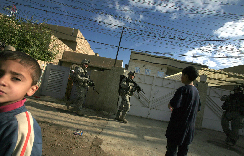 Description of . US soldiers from Alpha Company, 2nd Battalion, 3rd Infantry Regiment, 3rd Stryker Brigade Combat Team patrol the Beida neighborhood bordering Sadr City in Baghdad, Iraq Sunday,  Feb. 18, 2007. The soldiers are part of a surge of US troops brought to Baghdad as part of a plan to bring security to the city.  (AP Photo/Maya Alleruzzo)