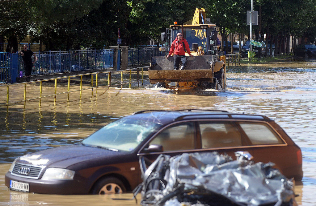 Description of . A man rides on a bulldozer through flooded streets of the town of Obrenovac, 40 kilometres west of Belgrade, on May 19, 2014. The Balkans braced for more misery as the death toll from the worst floods in a century rose to 47 and rising waters forced thousands more to flee their homes. Muddy waters from the Sava River have submerged houses, churches, mosques and roads in Bosnia, Serbia and Croatia after record rainfall wreaked havoc across the central European region.  AFP PHOTO / ALEXA  STANKOVIC/AFP/Getty Images
