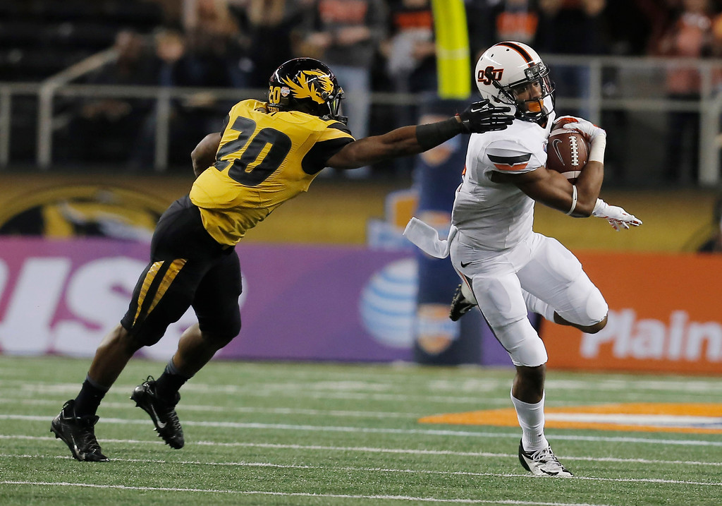 Description of . After intercepting the ball from Missouri quarterback James Franklin, Oklahoma State cornerback Justin Gilbert (4) gets past Missouri running back Henry Josey (20) during the first half of the Cotton Bowl NCAA college football game on Friday, Jan. 3, 2014, in Arlington, Texas. (AP Photo/Brandon Wade)