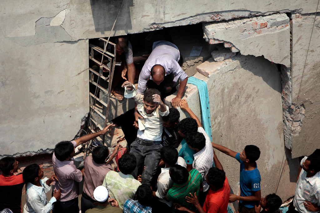 Description of . A man who was trapped in an eight-story building housing several garment factories is rescued after the structure collapsed in Savar, near Dhaka, Bangladesh, Wednesday, April 24, 2013. The building collapsed near Bangladesh's capital Wednesday morning, killing dozens of people and trapping many more in the rubble, officials said. (AP Photo/ A.M. Ahad)