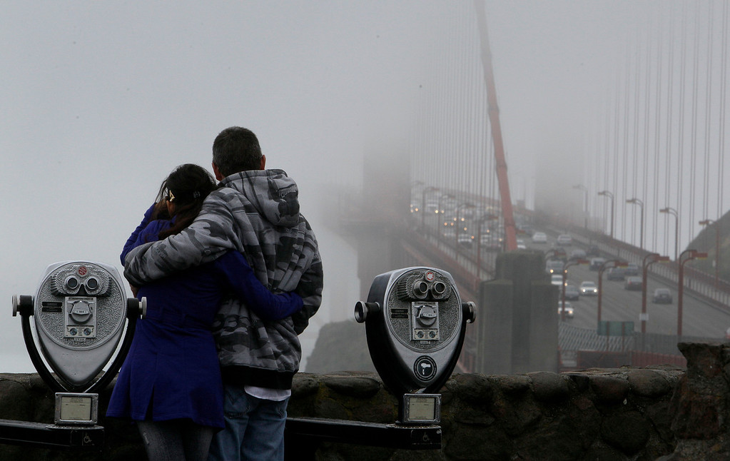 Description of . A couple looks toward the Golden Gate Bridge from a vista point in Marin County, Calif., Monday, June 6, 2011. (AP Photo/Jeff Chiu)
