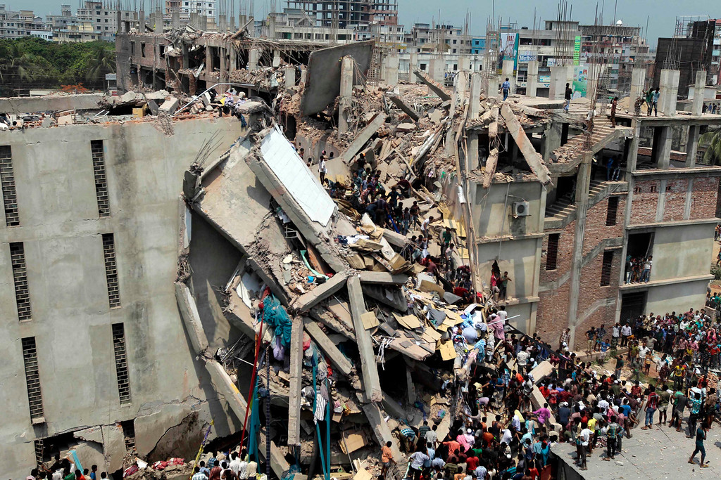 Description of . People and rescuers gather after an eight-story building housing several garment factories collapsed in Savar, near Dhaka, Bangladesh, Wednesday, April 24, 2013. (AP Photo/ A.M. Ahad)