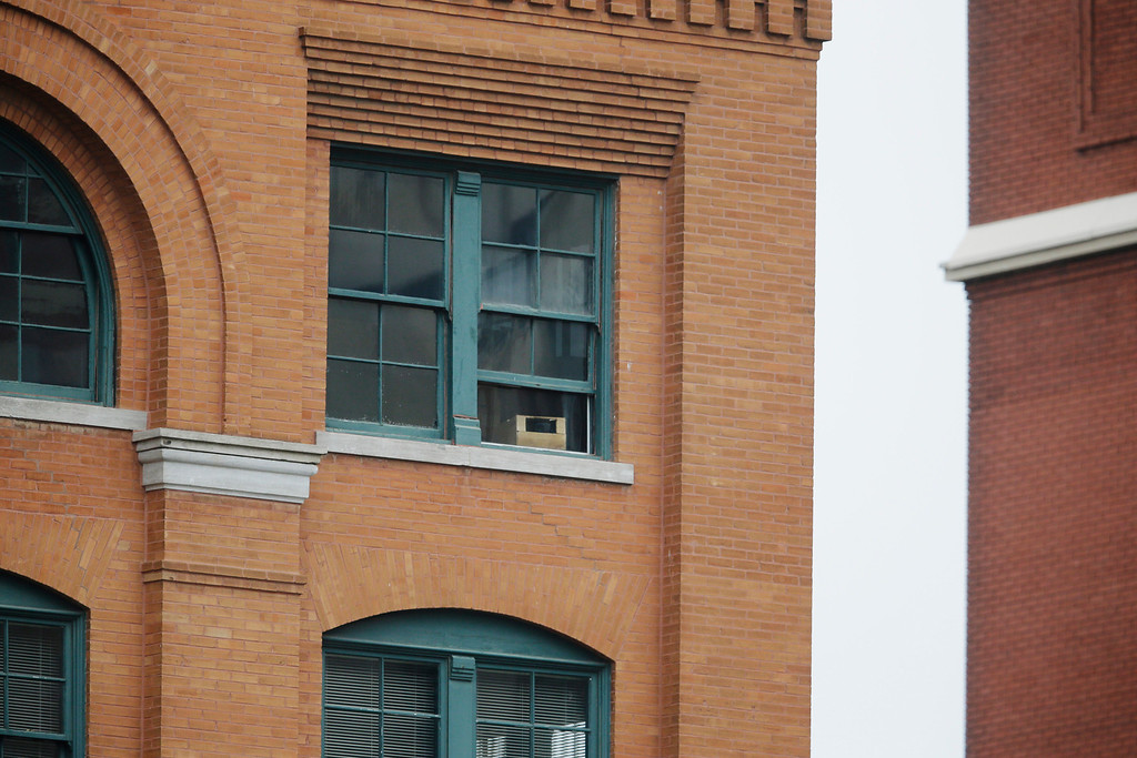 Description of . The window, center with box, at the Texas School Book Depository building where Lee Harvey Oswald stood to shoot at John F. Kennedy is seen before a ceremony to mark the 50th anniversary of Kennedy's  assassination, Friday, Nov. 22, 2013, at Dealey Plaza in Dallas. President Kennedy's motorcade was passing through Dealey Plaza when shots rang out on Nov. 22, 1963. (AP Photo/Tony Gutierrez)