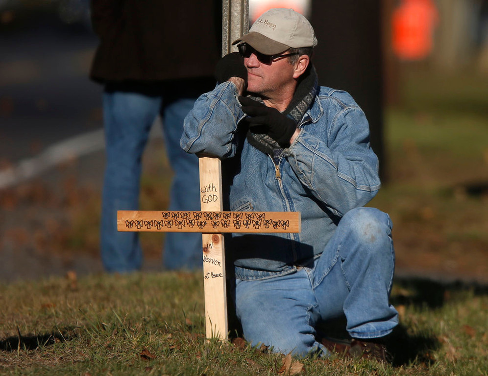 Description of . A mourner kneels with a cross marked with 26 angels across from the calling hours for Sandy Hook Elementary School principal Dawn Lafferty Hochsprung, Wednesday, Dec. 19, 2012, in Woodbury, Conn.  Hochsprung was killed when a gunman forced his way into Sandy Hook Elementary School in Newtown on Dec. 14 and opened fire, killing 26 people, including 20 children. (AP Photo/Jason DeCrow)