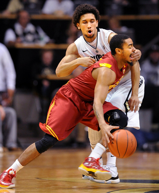 Description of . Southern California's Jio Fontan, front, tries to drive past Colorado's Askia Booker during the first half of their NCAA college basketball game, Thursday, Jan. 10, 2013, in Boulder, Colo. (AP Photo/The Daily Camera, Cliff Grassmick)