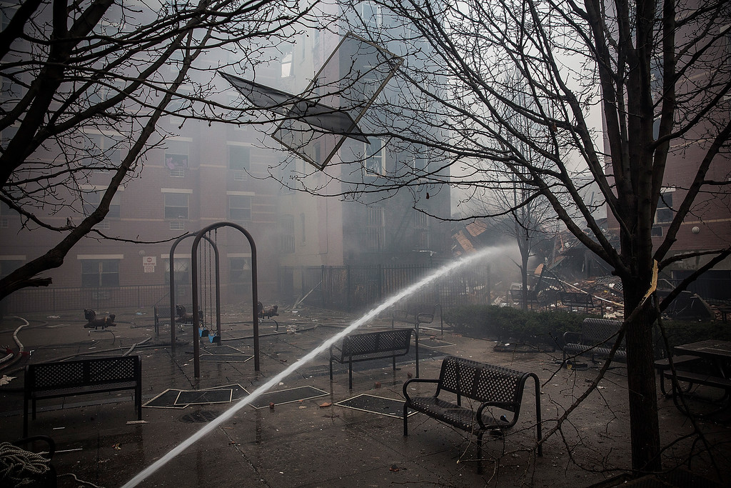 Description of . Water is sprayed on smoldering debris from a two building collapse on March 12, 2014 in New York City.  (Photo by Andrew Burton/Getty Images)