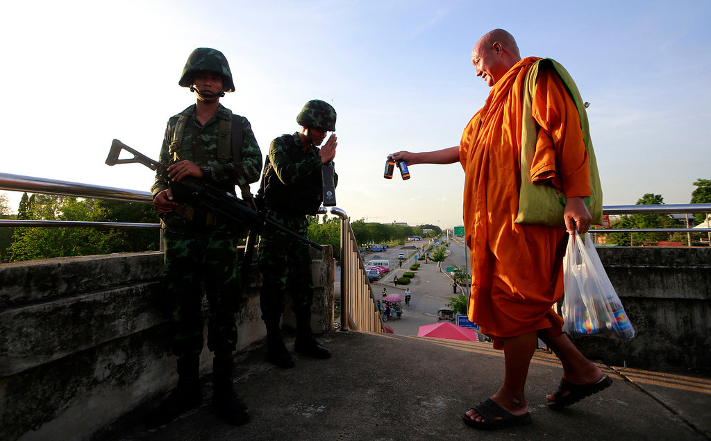. A Buddhist monk offers energy drink to Thai soldiers guarding a pedestrian overfly near the site where pro-government demonstrators stage a rally on the outskirts of Bangkok, Thailand Tuesday, May 20, 2014. (AP Photo/Wason Wanichakorn)