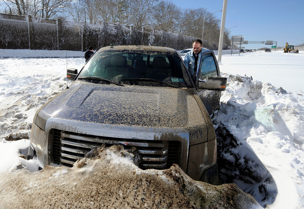 . Wayne Gingo, of Medford, N.Y., gets back into his car that got stuck in the snow on the Long Island Expressway eastbound near Exit 60, Saturday, Feb. 9, 2013, in Ronkonkoma, N.Y. Gingo was driving home from his job as a postal worker at JFK Airport and got stuck in the snow at 1:45 a.m. He spent the night in the car waiting for a tow truck. (AP Photo/Kathy Kmonicek)