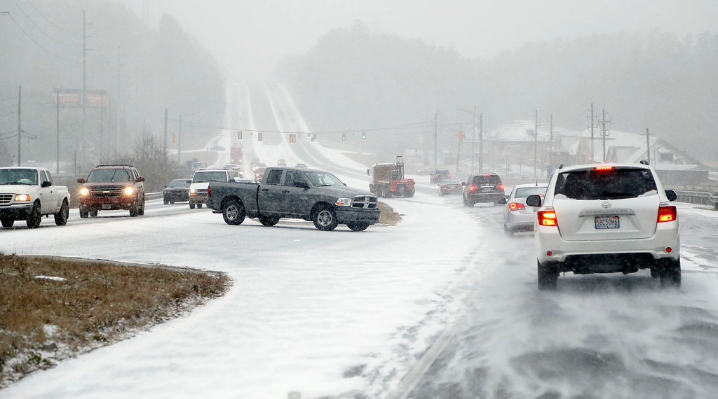 Description of . Vehicles travel on US highway 280 as snow begins to make driving conditions difficult Tuesday January 28,  2014 in Chelsea,  Ala. A fast-moving, unexpectedly severe winter storm blanketed much of Alabama with a treacherous layer of frozen precipitation Tuesday.  (AP Photo/Hal Yeager)