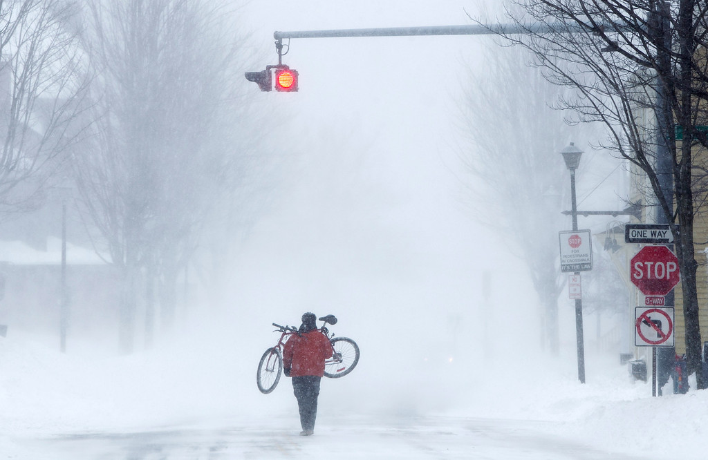 . Juan Tavares carries his bike rather than risk riding on a snow-covered street during a blizzard, Saturday, Feb. 9, 2013, in Portland, Maine. The storm dumped more than 30 inches of snow as of Saturday afternoon, breaking the record for the biggest storm on record. (AP Photo/Robert F. Bukaty)