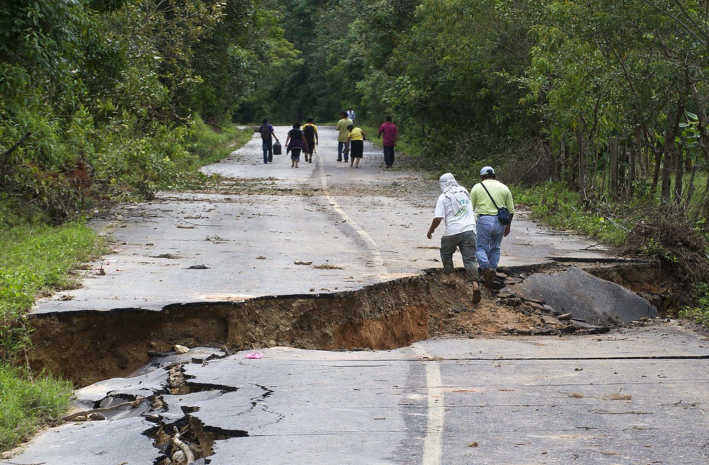 Description of . Residents walk along a road leaving La Pintada, state of Guerrero, Mexico, on September 19, 2013 as heavy rains hit the country. AFP PHOTO/RONALDO  Schemidt/AFP/Getty Images