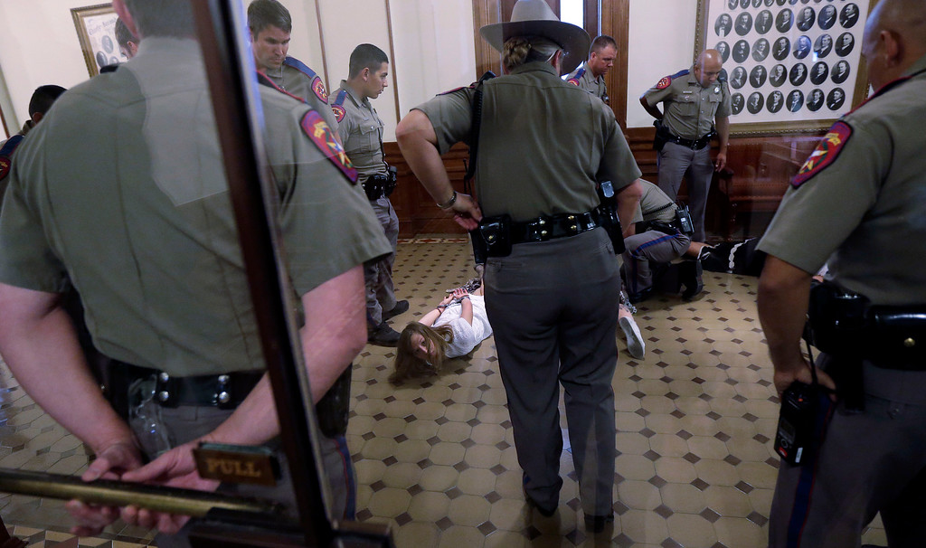 Description of . Texas state troopers stand over pro-abortion rights protesters after they were taken from the Texas Senate gallery as the Senate debates an abortion bill, Friday, July 12, 2013, in Austin, Texas. The bill would require doctors to have admitting privileges at nearby hospitals, only allow abortions in surgical centers, dictate when abortion pills are taken and ban abortions after 20 weeks. (AP Photo/Eric Gay)