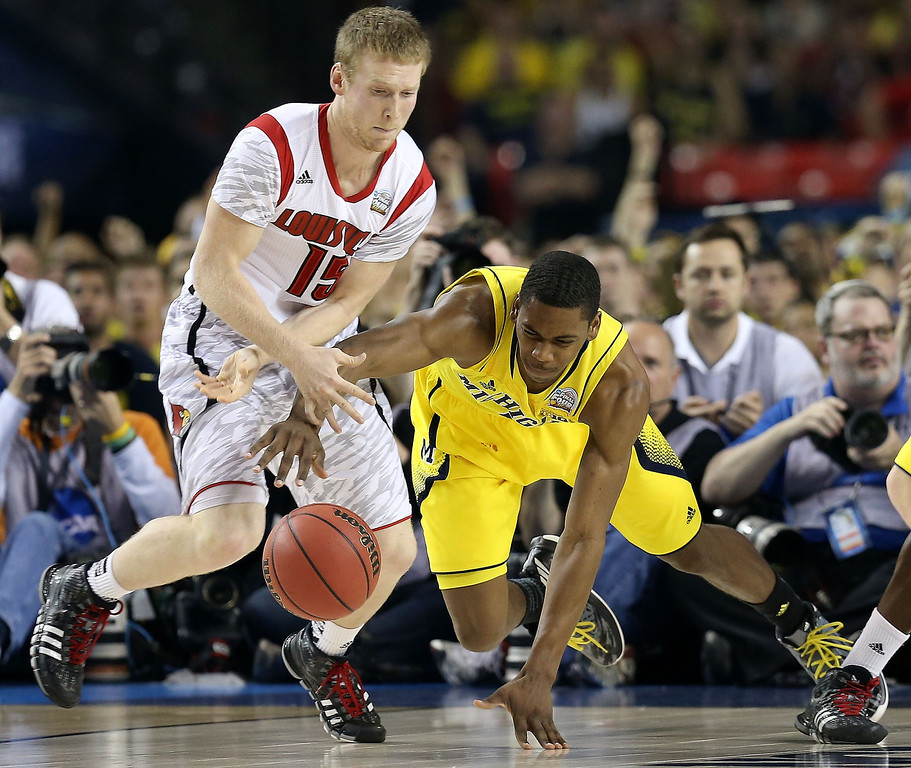 Description of . Tim Henderson #15 of the Louisville Cardinals and Glenn Robinson III #1 of the Michigan Wolverines go after a loose ball in the first half during the 2013 NCAA Men's Final Four Championship at the Georgia Dome on April 8, 2013 in Atlanta, Georgia.  (Photo by Streeter Lecka/Getty Images)