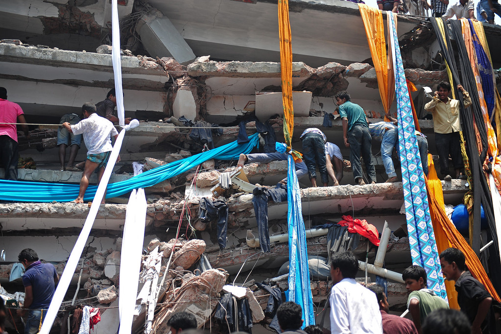 Description of . Bangladeshi volunteers prepare lengths of textiles to used as evacuation slides for the injured and dead after an eight-story building collapsed in Savar, on the outskirts of Dhaka, on April 24, 2013.   AFP PHOTO/Munir uz ZAMAN/AFP/Getty Images