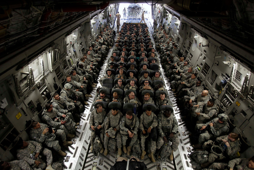 Description of . In this Nov. 30, 2010 photo, members of 1st Brigade, 3rd Infantry Division, based at Fort Stewart, Ga., sit in the belly of a C-17 aircraft at Sather Air Base in Baghdad as they begin their journey home after a year in Iraq. More than seven years after 1st Brigade entered Baghdad as the first conventional U.S. forces in Iraq, its soldiers were coming home from a yearlong deployment that saw the end of combat operations.  (AP Photo/Maya Alleruzzo)