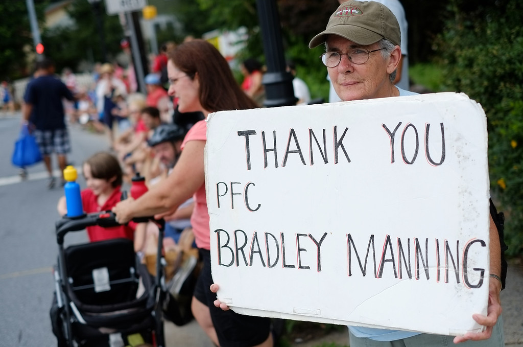 Description of . A woman shows her support for Bradley Manning during the Independence Day parade in Takoma Park, Maryland on July 4, 2013. Independence Day celebrates the declaration of independence from Britain in 1776. Manning who sent war logs and State Department cables to WikiLeaks, is charged with 21 offences, including aiding the enemy.  MANDEL NGAN/AFP/Getty Images