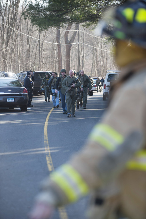 Description of . NEWTOWN, CT - DECEMBER 14:  Connecticut State Police walk on Dickson Street  from the scene of an elementary school shooting on December 14, 2012 in Newtown, Connecticut. According to reports, there are about 27 dead, 18 children, after a gunman opened fire in at the Sandy Hook Elementary School. The shooter was also killed.  (Photo by Douglas Healey/Getty Images)