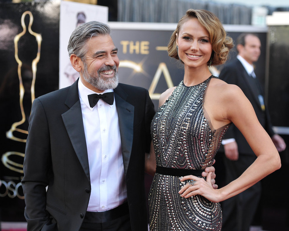Description of . Actor George Clooney, left, and Stacy Keibler arrive at the Oscars at the Dolby Theatre on Sunday Feb. 24, 2013, in Los Angeles. (Photo by John Shearer/Invision/AP)