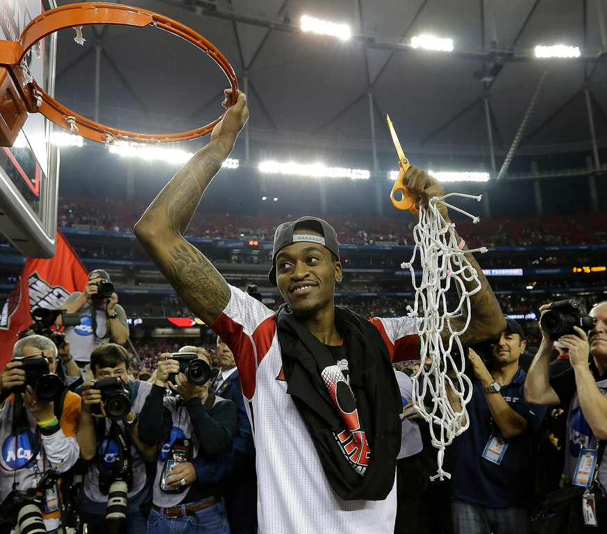 Description of . Louisville guard Kevin Ware holds the net after Louisville defeated Michigan 82-76 after the second half of the NCAA Final Four tournament college basketball championship game Tuesday, April 9, 2013, in Atlanta. (AP Photo/David J. Phillip)