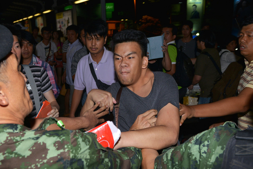 Description of . A protester scuffles with army soldiers while resisting arrest after an anti-coup rally on May 23, 2014 in Bangkok, Thailand. Several hundred anti-coup protesters rallied in Bangkok\'s shopping district, a day after the military seized control in a bloodless coup. (Photo by Rufus Cox/Getty Images)
