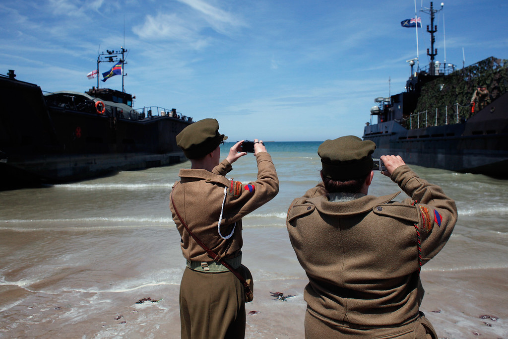 Description of . People wearing WWII military uniforms of Czechoslovakia take a snapshot of British landing craft, on the beach of Arromanches, western France , Friday June 6, 2014. (AP Photo/Thibault Camus)