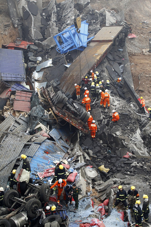 Description of . Rescuers work under the collapsed Yichang bridge near the city of Sanmenxia, central China's Henan province, on February 1, 2013. A fireworks-laden truck exploded as it crossed a bridge in central China on Friday, killing 26 people as the structure collapsed and vehicles plummeted to the ground, state-run media reported. An 80-metre long part of the bridge collapsed and six vehicles had been retrieved from the debris, China's official news agency Xinhua said. The bridge near the city of Sanmenxia is on the G30 expressway, the longest road in China, which stretches for nearly 4,400 kilometers (2,700 miles) from China's western border with Kazakhstan to the eastern Yellow Sea.      AFP PHOTO  STR/AFP/Getty Images
