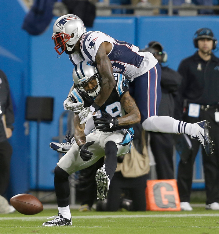 . New England Patriots\' Kyle Arrington, top, knocks the ball from Carolina Panthers\' Ted Ginn, bottom, during the first half of an NFL football game in Charlotte, N.C., Monday, Nov. 18, 2013. (AP Photo/Gerry Broome)