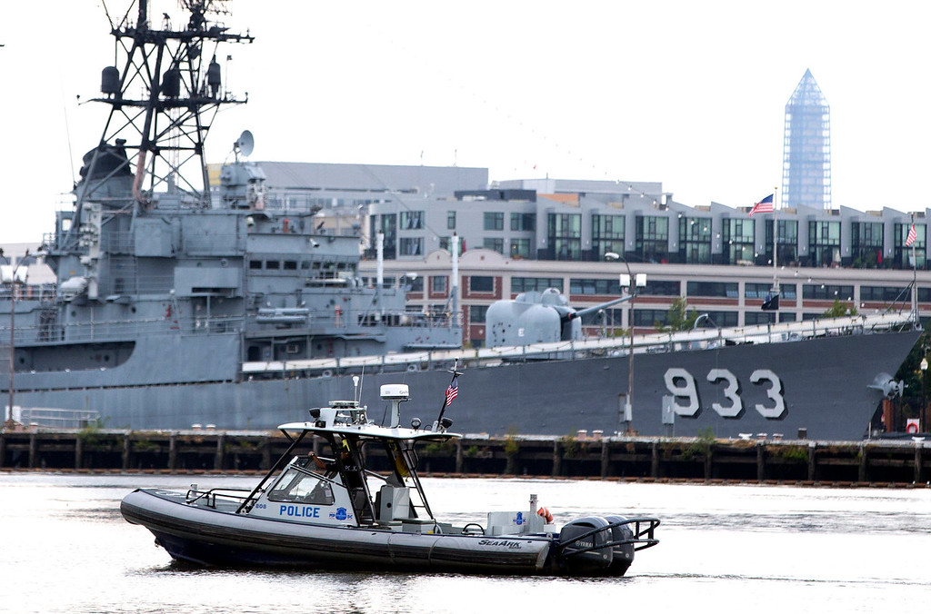 Description of . A police boat patrols near the scene of a shooting at the Washington Navy Yard on Monday, Sept. 16, 2013, in Washington. At least one gunman opened fire inside a building at the Washington Navy Yard, and officials said six people were killed and as many as 10 were wounded, including a law enforcement officer. (AP Photo/ Evan Vucci)