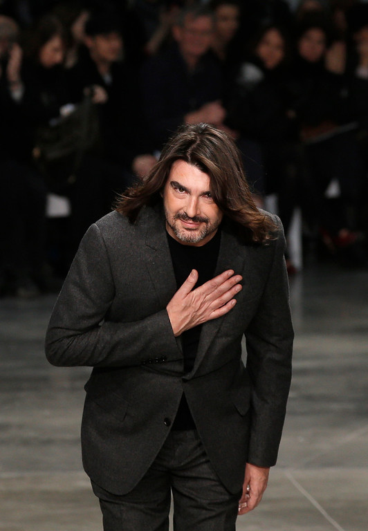 Description of . French fashion designer Stephane Rolland reacts after the presentation of his Spring Summer 2013 Haute Couture fashion collection, presented in Paris, Tuesday, Jan.22, 2013. (AP Photo/Christophe Ena)